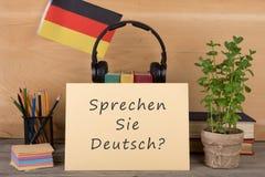 与文本& x22的纸; sprechen sie德意志?& x22; 德国的旗子,书,耳机,铅笔 库存照片