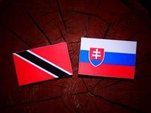 与斯洛伐克的旗子的特立尼达和多巴哥旗子在树桩iso 免版税图库摄影