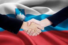 与斯洛文尼亚的旗子的合作握手 免版税库存图片