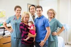 与新出生的女婴和父母的医疗队 免版税库存图片