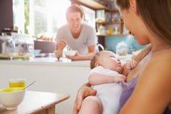 与新出生的小女儿的家庭在早餐桌上 免版税库存图片