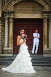 与新娘和新郎的婚礼照片 摆在新郎和天主教的背景的美丽的年轻新娘 免版税库存图片