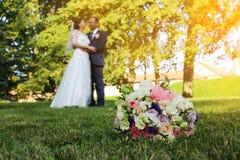 与新婚佳偶背景的,新娘和新郎的婚礼花束 库存照片
