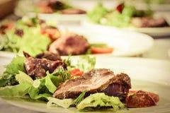 与新沙拉混合的烤牛肉和蕃茄在白色p服务 库存图片
