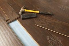 与新的层压制品的地板的锤子和块 库存图片