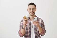 与新的app的付帐可笑地是容易 感情和激动的英俊的人画象举行信用的玻璃的 免版税图库摄影