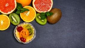 与新鲜水果猕猴桃、桔子和樱桃的自创微型馅饼在页岩板 抛糖 顶视图,文本的空间 免版税库存图片