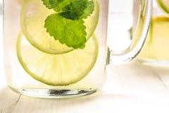 与新鲜的冷的冰、柠檬和薄荷叶的柠檬水鸡尾酒Mojito在金属螺盖玻璃瓶 免版税库存照片