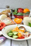 与新鲜的成熟夏天菜的素食健康沙拉:蕃茄、黄瓜、胡椒和葱在轻的木背景 免版税库存照片