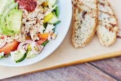 与新鲜的成份的五颜六色的沙拉沿着切的面包 库存照片
