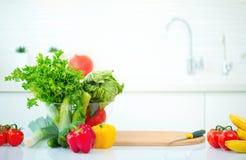 与新鲜的有机蔬菜和水果的厨房用桌 免版税图库摄影