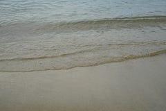 与新鲜的清楚的海水的软的淡色干净的沙滩和光泡影挥动在Ornos岸的线背景和copyspace 免版税库存照片