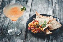 与新鲜的芒果辣调味汁和在家做的玉米片的辣玛格丽塔酒 免版税库存照片