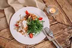 与新鲜的芝麻菜和蕃茄的健康鸡丁沙拉在一张木桌上 免版税图库摄影