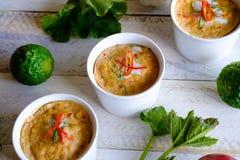 与新鲜的草本盘的泰国蒸的海鲜咖喱 免版税库存图片