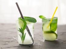 与新鲜的鸡尾酒的两块玻璃由冰制成在窗口前面的具体桌 库存图片