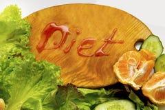与新鲜的莴苣菜的构成和果子和切板有题字的节食 库存照片