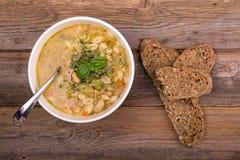 与新鲜的pesto和棕色种子面包的蔬菜通心粉汤 库存照片