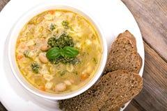 与新鲜的pesto和棕色种子面包的蔬菜通心粉汤 库存图片