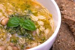 与新鲜的pesto和棕色种子面包的蔬菜通心粉汤 免版税图库摄影