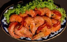 与新鲜的rosmarin和柠檬汁的油煎的大虾 免版税库存照片