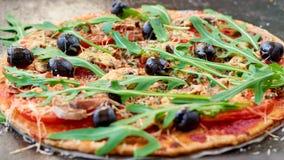 与新鲜的rucola、蕃茄和黑橄榄的鲜美自创素食薄饼在黑暗的桌关闭 健康素食者快餐 库存图片