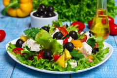 与新鲜蔬菜、希腊白软干酪和黑橄榄的希腊沙拉在木背景 库存照片