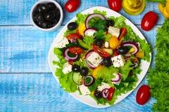 与新鲜蔬菜、希腊白软干酪和黑橄榄的希腊沙拉在木背景 免版税库存图片