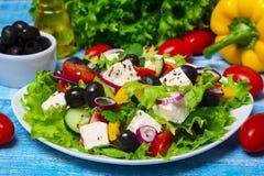 与新鲜蔬菜、希腊白软干酪和黑橄榄的希腊沙拉在木背景 免版税图库摄影