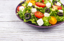 与新鲜蔬菜、希腊白软干酪和黑橄榄的希腊沙拉 库存照片