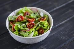与新鲜蔬菜、庭院草本和各式各样的蕃茄的沙拉在一个白色碗 库存照片