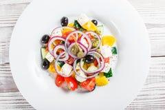 与新鲜蔬菜、橄榄和希腊白软干酪的希腊沙拉在木背景关闭 库存图片