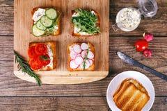 与新鲜蔬菜、蕃茄、黄瓜、萝卜和芝麻菜的四个三明治在木背景 自创黄油 免版税图库摄影