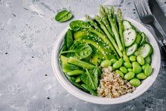 与新鲜蔬菜和奎奴亚藜,菠菜,鲕梨,芦笋,黄瓜, edamame豆的绿色素食主义者菩萨碗沙拉 免版税库存照片