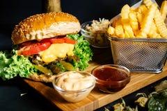 与新鲜蔬菜和炸薯条的烤牛肉汉堡在地方小餐馆服务了热 库存图片