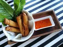 与新鲜蔬菜和甜辣味番茄酱的酥脆春卷在木盘子 免版税库存图片