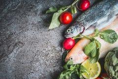 与新鲜蔬菜成份的两条未加工的鳟鱼鱼健康干净烹调的,顶视图 免版税库存图片