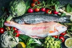 与新鲜蔬菜成份的两条未加工的鳟鱼鱼健康干净烹调的 免版税图库摄影