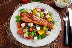 与新鲜蔬菜沙拉,希腊白软干酪的油煎的鲑鱼排 概念健康食物 免版税库存图片