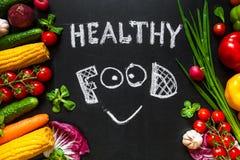 与新鲜蔬菜的健康食物概念烹调的 与微笑的标题`健康食物`由白垩写在背景 库存照片