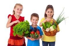 与新鲜蔬菜的微笑的孩子 免版税库存图片