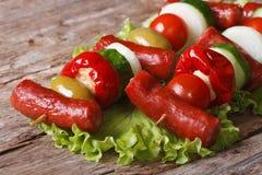 与新鲜蔬菜的油煎的香肠在水平的串 免版税库存图片