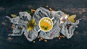 与新鲜蔬菜的玉米汤在碗 健康的食物 在黑木背景 免版税库存图片