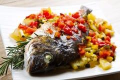 与新鲜蔬菜的被烘烤的鱼 库存照片