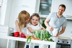与新鲜蔬菜的年轻家庭在厨房里 免版税库存图片