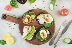 与新鲜蔬菜,鸡蛋,鲕梨,蕃茄,在轻的大理石桌上的黑麦面包的夏天三明治 顶面vew 党的开胃菜 fla 库存图片
