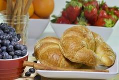 与新鲜水果碗的新月形面包午餐的 库存图片