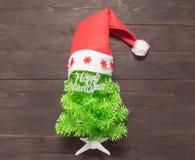 与新年快乐按摩的圣诞树和红色帽子打开  免版税库存照片
