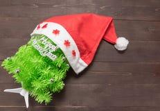 与新年快乐按摩的圣诞树和红色帽子打开  免版税库存图片