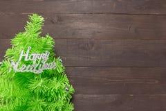与新年快乐按摩的圣诞树在木b 免版税图库摄影